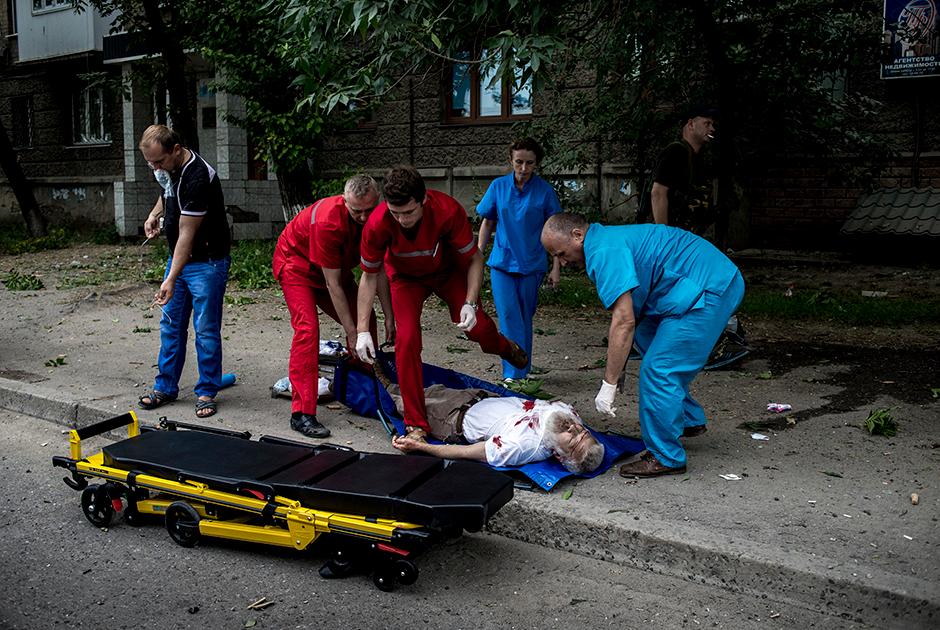 Врачи скорой оказывают помощь пострадавшему во время обстрела