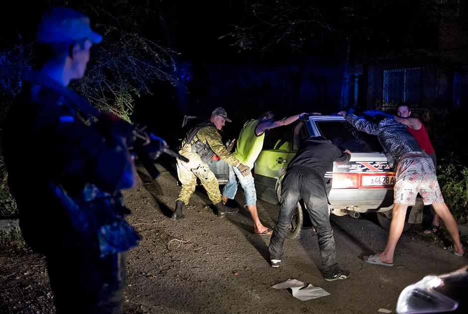 Сотрудник группы быстрого реагирования проверяет задержанных во время патрулирования Луганска в комендантский час