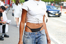 Одна из гостей модных шоу, похоже, с особой тщательностью следила за новейшими трендами: задранные повыше трусы, выглядывающие из-под рваных мешковатых джинсов в стиле 2000-х, белая майка, завязанная на узел, очень маленькая сумка и крупные серьги-кольца тут же выдают в ней хайпбиста. А надменное выражение лица только дополняет этот образ.