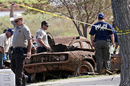 In this Sept. 18, 2013 file photo, law enforcement officials from multiple agencies examine the two cars pulled from Foss Lake, in Foss, Okla. The state medical examiner released autopsy reports identifying two of the bodies as 16-year-old Jimmy Allen Williams and 42-year-old Cleburn Hammack. They were among the remains of six bodies found the in two cars