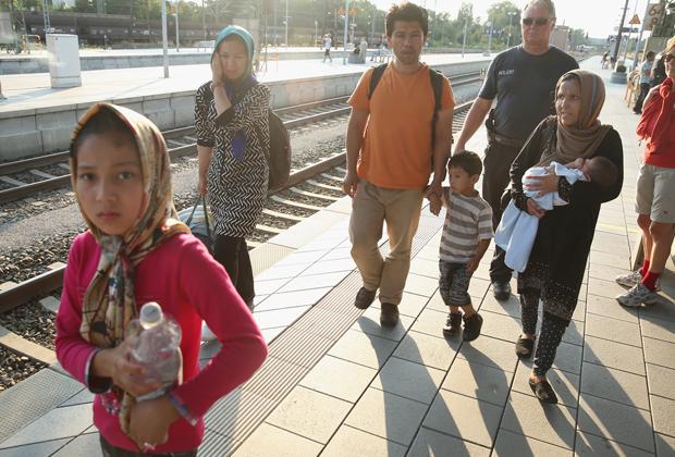 Полиция ведет в центр приема семью нелегалов из Афганистана, 2015 год
