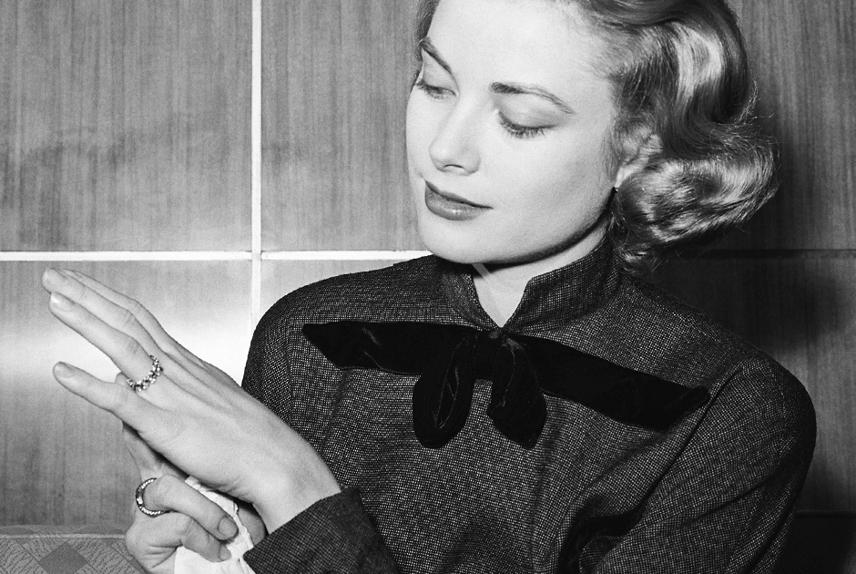Грейс Келли демонстрирует свое обручальное кольцо, которое князь Ренье подарил ей в Чикаго. Правитель Монако сопровождал ее во время работы над фильмом «Высшее общество», ставшим последним в ее карьере