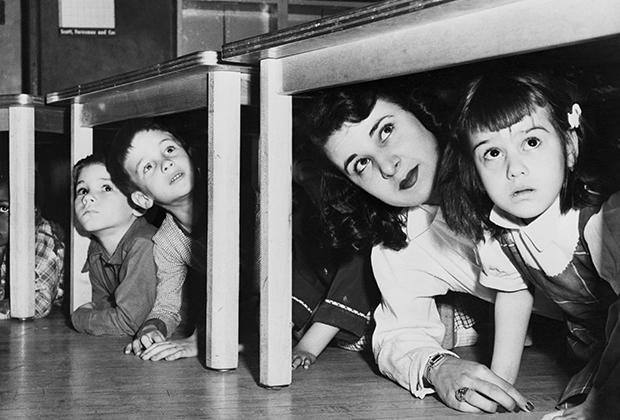 Дети с воспитательницей прячутся под столами после сигнала тревоги
