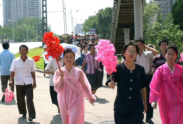 Люди собираются на улицах Пхеньяна для встречи Ким Чен Ира, возвращающегося из России, 2002 год