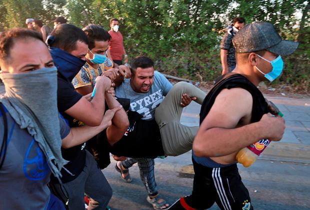 Протестующие несут мужчину, раненного во время демонстрации в Багдаде 5 октября