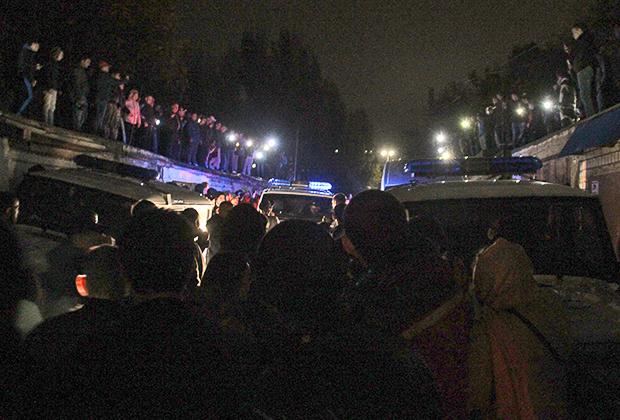 Местные жители и сотрудники полиции около гаражного комплекса, где было найдено тело пропавшей девятилетней девочки