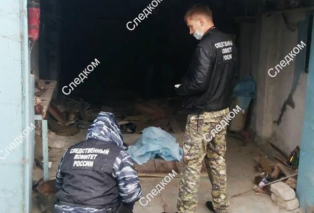 Сотрудники СКР во время осмотра гаража, где была убита девятилетняя девочка