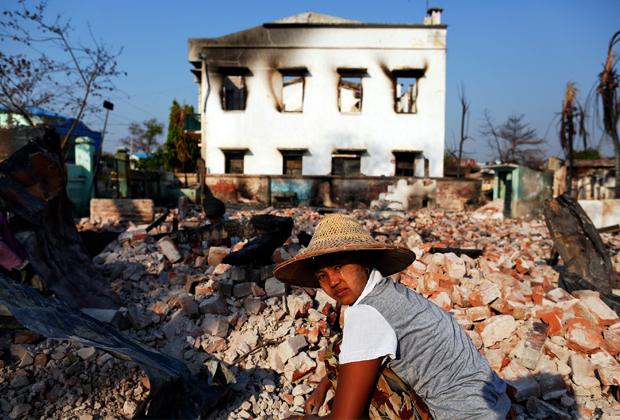 Женщина среди руин сожженных мусульманских домов в бирманском городе Мейтхила, 2013 год