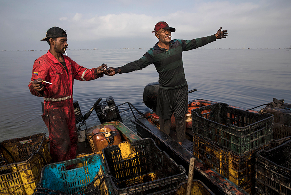 Краболовы, чья одежда и снаряжение пропитаны нефтью, устраивают перекур на озере Маракайбо