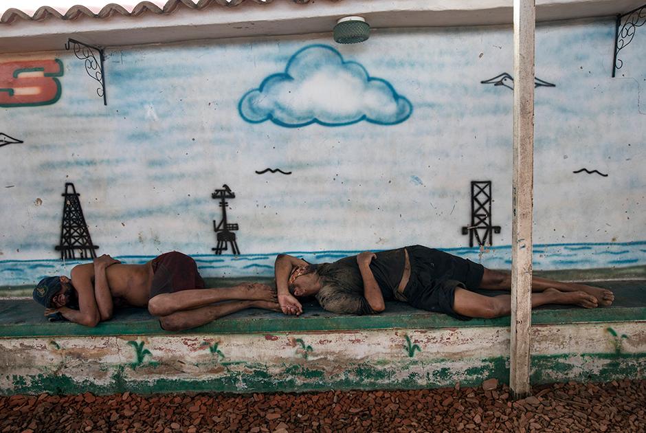 Рыбаки спят после работы перед рисунком с озером Маракайбо и нефтяными вышками