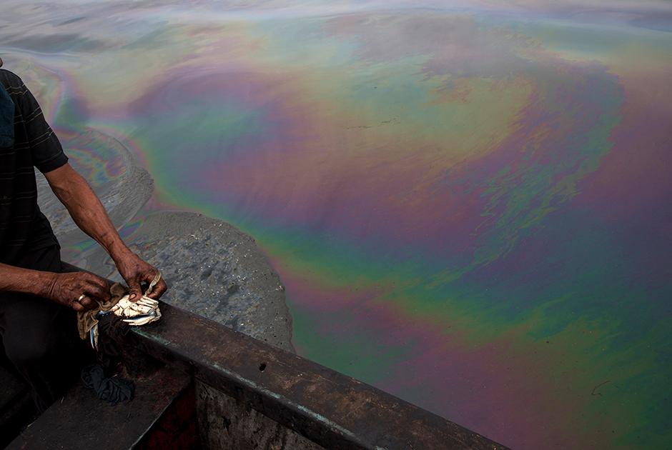 Рыбак очищает только что пойманного краба от нефти на пляже Пунта-Горда в Кабимасе