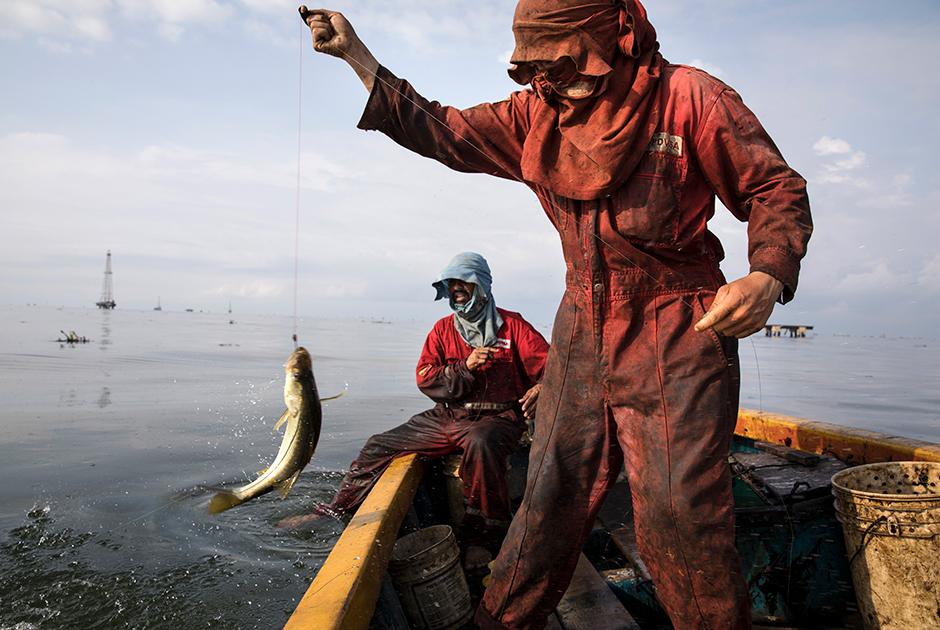 Рыбаки в униформе крупнейшей нефтегазовой компании Венесуэлы PDVSA ловят макловину, известную также как «робало», возле терминала отгрузки сырой нефти La Salina на озере Маракайбо, недалеко от Кабимаса