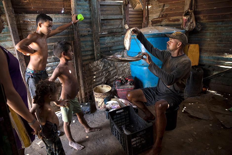 Рыбак Алехандро в испачканной нефтью одежде взвешивает улов после рабочего дня на озере