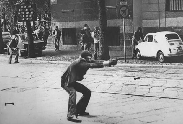 Участник протеста целится из пистолета в полицейских. Милан, 1977 год