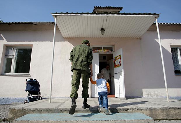 Житель Донецка ведет ребенка в школу, 2015 год