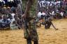 Страна Либерия и регион реки Мано в Западной Африке уже много лет находятся в состоянии гражданской войны, и международное сообщество поддерживает различные программы по укреплению стабильности и долгосрочного мира. Одно из таких объединяющих событий — фестивали, посвященные мирному сосуществованию и взаимному уважению между различными культурами региона. Как раз на таком трехдневном фестивале на окраине Монровии и было сделано это фото. <br> <br> Фотограф Джонатан Бэнкс сначала снимал солдат, однако потом обратил внимание на толпу вокруг них. «Я кружил вокруг этого конкретного солдата, когда почувствовал, что что-то происходит позади. Вдруг из толпы высунулся этот мальчик и потянулся за своим драгоценным мячиком. Это был ребенок, выросший на войне, и у него были все основания бояться солдат и их оружия. Он хотел вернуть мяч, но его взгляд был прикован к солдату», — пояснил художник. Это секундное движение запечатлено в фотографии, которая  изображает ненадежность мира, отраженную в глазах маленького ребенка, мало понимающего происходящее. Все, что он знал точно, — что он хотел вернуть свой мяч и при этом остаться в безопасности. Снимок стал абсолютным призером премии.