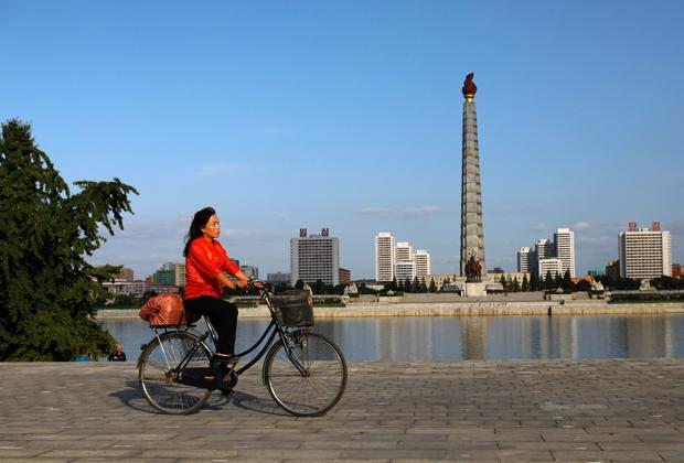 Женщина на велосипеде на фоне монумента идеям чучхе в Пхеньяне
