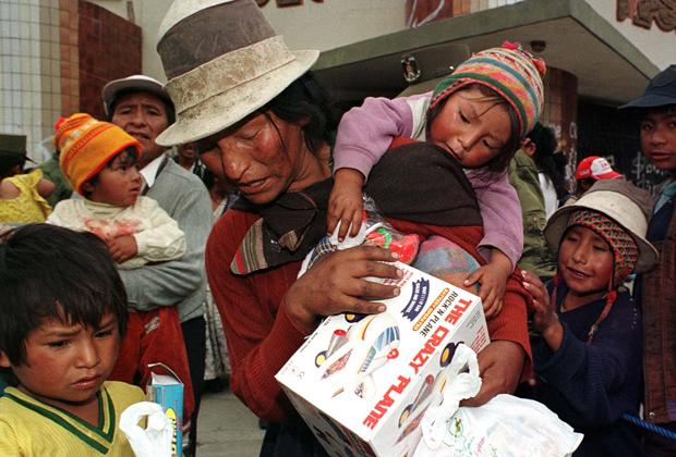 Женщина-представитель коренного населения несет со своими детьми подарки на Рождество бедным детям столицы Ла-Пас