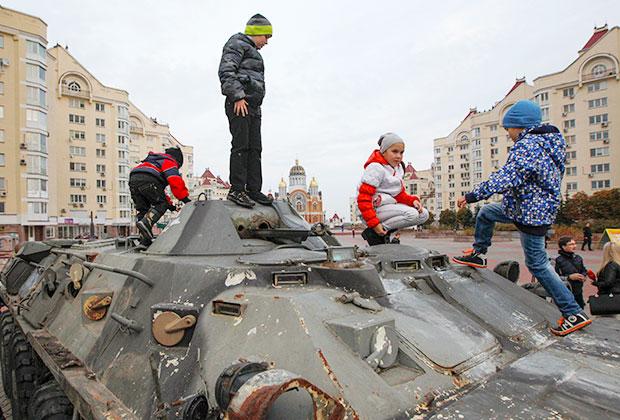 Дети играют с подбитым БТР, привезенным в Киев с Донбасса в качестве трофея. Октябрь 2014 года