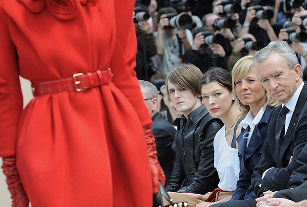 Бернар Арно, его вторая жена Элен-Мерсье Арно и актриса Мила Йовович на показе коллекции Louis Vuitton сезона осень-зима 2009 в рамках Парижской недели моды. Арно лично посещает важнейшие события в жизни своих брендов, а порой и сам выбирает места для ключевых магазинов.