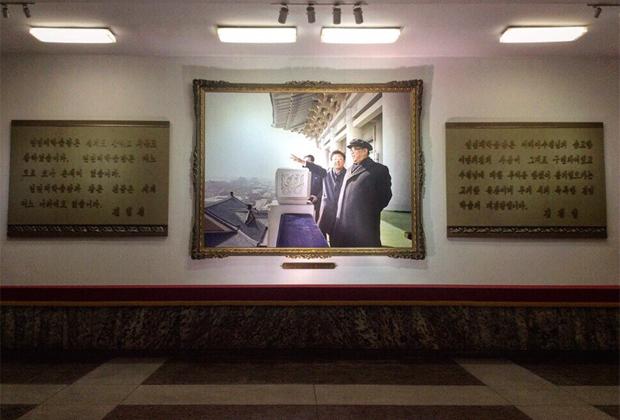 Совместный фотопортрет Ким Ир Сена и Ким Чен Ира в Народном дворце учебы в Пхеньяне. По бокам от фотопортрета — цитаты вождей