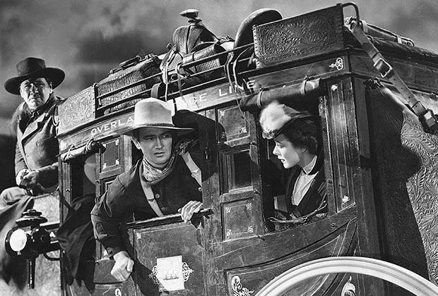 Джон Уэйн в фильме «Дилижанс» 1939 года. Этот фильм был показан в Советском Союзе под названием «Путешествие будет опасным». Уэйн предстает в образе классического обитателя Запада: стетсон, брюки на подтяжках, шейный платок и рубашка без рукавов