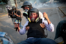 Пострадавшего сотрудника СМИ уносят во время акции протеста против правительства президента Венесуэлы Николаса Мадуро, приуроченной к празднику Первомая в Каракасе. Акция началась с неудачной попытки переворота со стороны лидера оппозиции. «День прошел, наполненный слезоточивым газом, резиновыми пулями, камнями, бутылками с зажигательной смесью и боевыми патронами», — вспоминают очевидцы. Во второй половине дня чиновники задержали протестующего с самодельным минометом. Полиция велела сотрудникам СМИ отойти, однако местный тележурналист Грегори Хаймес проигнорировал предупреждение. Национальная гвардия активировала устройство и бросила в Хаймеса. Он не понял, что произошло, пока не выплюнул кровь в противогаз, — челюсть была поражена шрапнелью. Коллеги бросились на помощь.