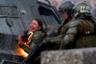 Фотография была сделана в Сантьяго 4 ноября 2019 года во время акции протеста против правительства Чили. В течение нескольких недель окрестности у станции метро «Бакедано» были эпицентром оппозиционных выступлений. Сквозь водяные пушки и плотные облака слезоточивого газа фотограф краем глаза заметил вспышку: там стояла охваченная пламенем женщина-полицейская, а ее товарищи пытались погасить огонь. Позднее ее увезли в больницу. Толпа яростно шумела, пытаясь забросать камнями полицейскую машину. Силовики отреагировали резиновыми пулями и газом. Протесты в тот день продолжались до глубокой ночи.