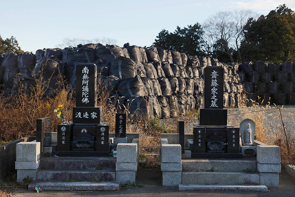 Сейчас радиоактивные отходы после дезактивации земель в префектуре Фукусима хранят в огромных черных мешках. Их свозят на территории специальных временных хранилищ в Футабе и соседней Окуме.  <br></br> Только в 2019 году в эти районы должны были свезти 5 миллионов тонн отходов, причем 4 миллиона из них — в Футабу. В будущем радиоактивный мусор должны отсортировать: часть сожгут, остальное захоронят на 30 лет в специальном хранилище. А до тех пор ряды черных мешков будут и дальше «расти» на рисовых полях и «оживлять» виды местных кладбищ.