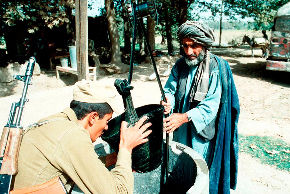 Советский солдат пьет воду из ведра местного жителя, 1986 год