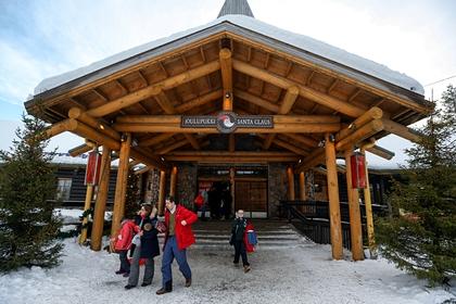 Туристы возле резиденции Санты на территории деревни Санта-Клауса в Рованиеми в Финляндии