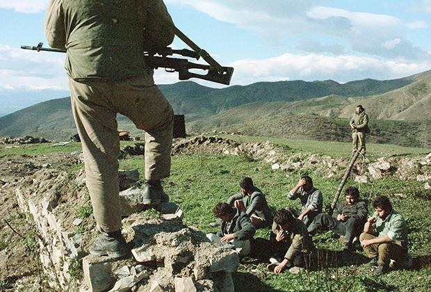 Боец с винтовкой охраняет задержанных армян.