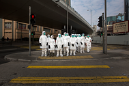 Health officers in full protective gear wait to cross a road near a wholesale poultry market in Hong Kong January 28, 2014. Hong Kong began culling 20,000 chickens and suspended imports of fresh poultry from mainland China for 21 days on Tuesday after the discovery of the H7N9 bird flu virus in a batch of live chicken from the southern province of Guangdong. REUTERS/Tyrone Siu (CHINA - Tags: HEALTH ENVIRONMENT SCIENCE TECHNOLOGY ANIMALS TPX IMAGES OF THE DAY) - GM1EA1S0YMZ01