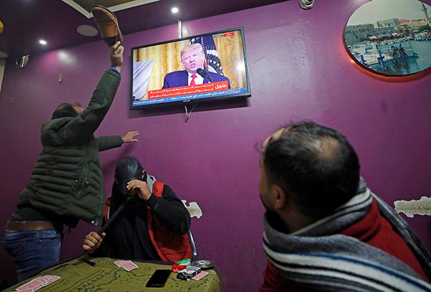 Палестинец в оккупированном Израилем Хевроне бьет ботинком изображение американского президента Дональда Трампа