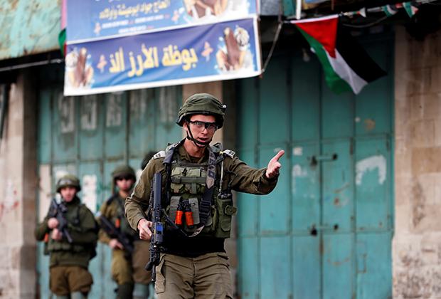 Израильский солдат во время протеста палестинцев из-за решения США признать законность нового еврейского квартала в городе Хеврон, конец 2019 года