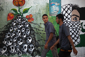 "Men walk past newly painted murals on  the 64th anniversary of ""Nakba"", Arabic for catastrophe, the term used to mark the events leading to Israel's founding in 1948, in Gaza City, Tuesday, May 15, 2012. Hundreds of thousands of Palestinians fled or were forced from their villages during the war over Israel's 1948 creation, an event they commemorate every year as their ""Nakba"". (AP Photo/Dusan Vranic)"