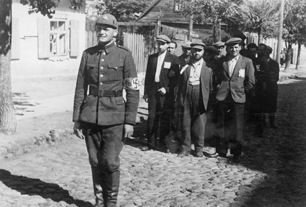 Полицай ведет евреев по вильнюсскому гетто. Июль 1941 года