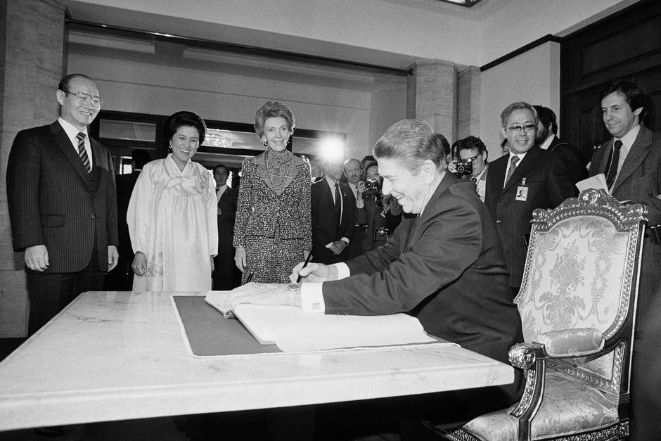 Рональд Рейган оставляет запись в гостевой книге в резиденции президента Южной Кореи в 1983-м. На заднем фоне — Чон Ду Хван и супруги глав государств