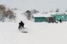Жители Материка приноровились передвигаться по улицам с многочисленными подъемами и спусками на специальных санках, которые цепляются к снегоходу. И нескучно, и экологично!