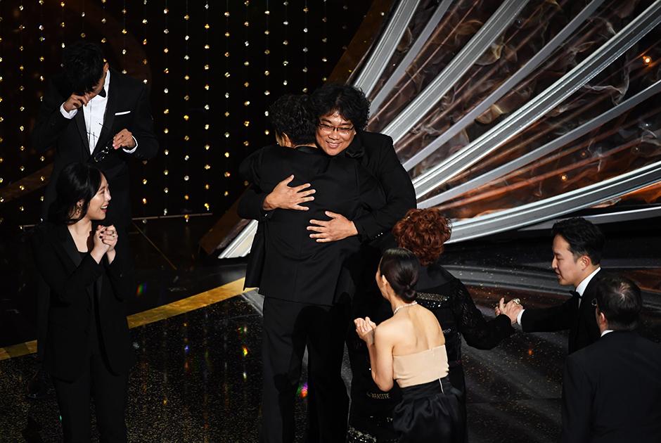 «Паразиты» стали первым в истории победителем «Оскара» в категории «Лучший фильм», который был снят не на английском языке. В прошлом мае картина Пон Джун-хо, которая иллюстрирует классовое расслоение через историю одной бедной семьи, втирающейся в доверие сеульским богачам, уже выигрывала «Золотую пальмовую ветвь» на Каннском фестивале — а на «Оскаре» удостоилась сразу четырех наград, победив также в номинациях «Лучший иностранный фильм», «Лучший оригинальный сценарий» и «Лучший режиссер».