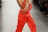 Обычно на публике топлес появляется Эмили Ратаковски, однако на дебютном показе 22-летней дизайнерши Тии Адеолы (Tia Adeola) свой накачанный торс показала совсем другая модель. Он прошелся по подиуму в брюках модного в 2020 году ярко-оранжевого цвета с оборками на вырезах штанин и в кроссовках в стиле колор-блок. Незамысловатый образ дополняли прозрачные перчатки того же цвета и длинные бусы.
