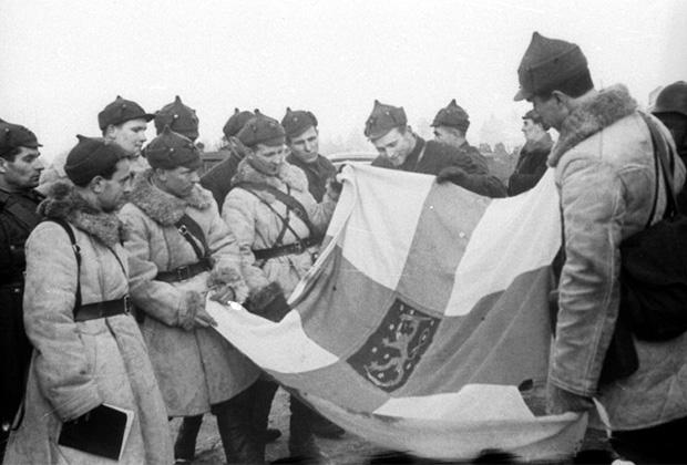 Группа советских командиров и бойцов осматривает отбитое у финнов знамя шюцкора (военизированной организации-ополчения), 1939 год. Фотограф Э. Хайкин