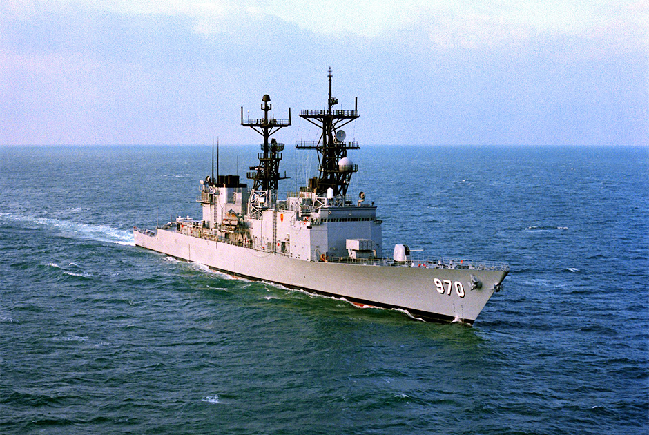 An aerial starboard bow view of the Spruance class destroyer USS Caron (DD-970) underway, 1/1/1983