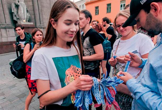 Девушка раздает ленточки с национальным орнаментом