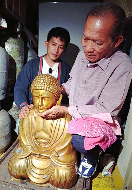 Сын Рогелио Рохаса со статуей Будды из бронзы и свинца. 1996 год