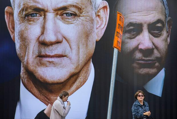 Люди на фоне плаката оппозиции. На первом плане — Бени Ганц, на втором — Нетаньяху