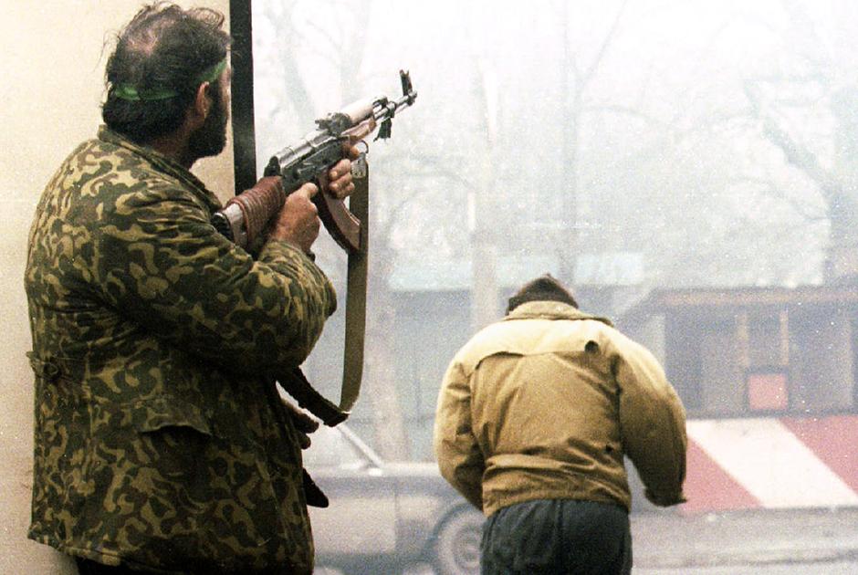 Чеченский боевик стреляет в направлении позиций федеральных войск в центре Грозного