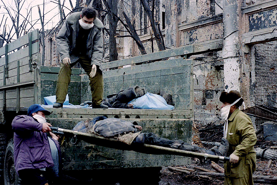 Два человека загружают тела людей в кузов грузовика. Грозный, 17 февраля 1995 года