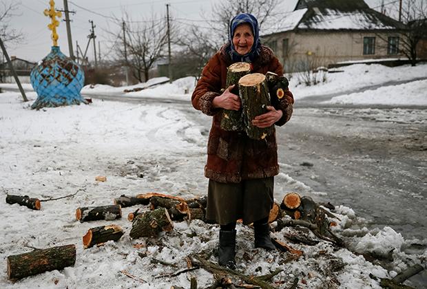 Пенсионерка собирает распиленное дерево на дрова. Авдеевка, подконтрольная Киеву часть Донбасса