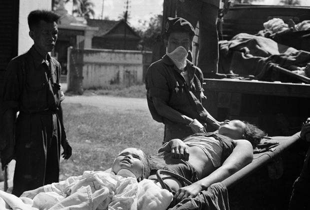 Пострадавшие во время боев в Лаосе женщина и ребенок. Декабрь 1960 года